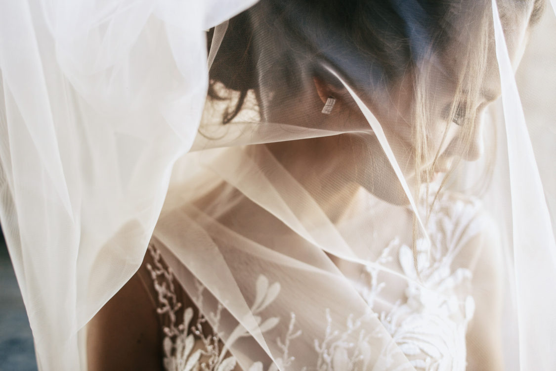Light veil hides tender young bride